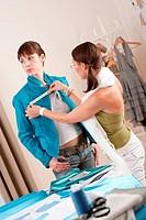 Female fashion designer measuring jacket on model