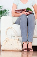 Part of a cute Woman on a sofa with a bag and a magazine