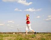 junge frau beim joggen auf einem feldweg