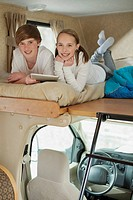 Siblings using computer technology in camper.