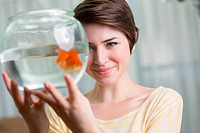 Young woman holding goldfish in a bowl