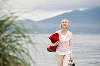 Senior woman walking along waterfront.