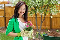 Pretty woman with flowers to plant in yard.