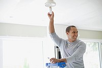 Young adult latino man replacing lightbulb.