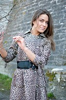 girl in leopard coat standing on the street, near the wall