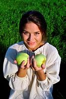 girl in a linen shirt, holding apples