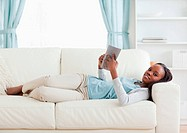 Woman lying on couch reading a book