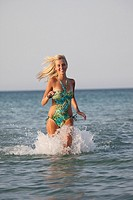 Healthy young woman running out of the sea