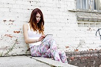 Young, red_haired girl with a Tablet PC