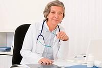 Senior doctor female sit behind office desk