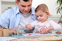 Young girl coloring with dad