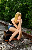 Attractive glum woman sitting on a suitcase on railway tracks in summer