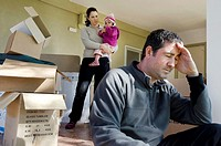 Young parents and their daughter stand beside cardboard boxes outside their home  Concept photo illustrating divorce, homelessness, eviction, unemploy...