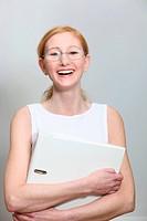 Lachende, junde Frau mit Brille und Aktenordner