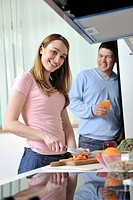 happy young woman with apple in kitchen and other food and vegetables