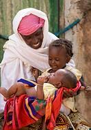 Ouagadougou, Burkina Faso: July 3, 2007. A Fulani woman in Ouagadougou, Burkina Faso, holds her two youngest children on her lap.
