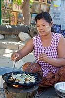 Myanmar, Burma  Mingun, near Mandalay  Street-food Vendor Frying Doughy Snacks  She is wearing thanaka paste on her face, a cosmetic sunscreen