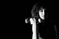 young woman practicing fitness and working out in a gym with dumbbell, weight lifting concept.