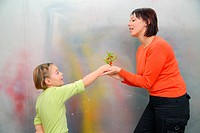 little girl giving gift to mother