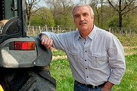 Farmer leaning against tractor