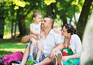 Happy young Family at park relaxing and have fun with pregnant woman