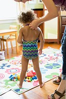Mother putting bathing suit on daughter