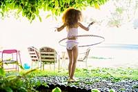 Mixed race girl twirling plastic hoop