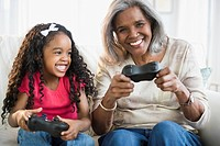 African American grandmother and granddaughter playing video games