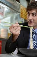 Businessman eating noodles in cafe
