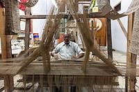 India, Uttar Pradesh, Banaras, Man weaving loom