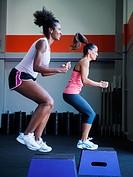 Two women in step aerobics class