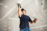 Drywall worker taping and mudding joint in ceiling