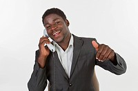 Young black man in a suit making a phone call in an office, smiling with a thumbs up gesture