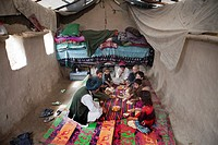 Afghan family having lunch in their mud house