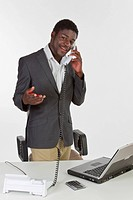 Young dark-skinned man standing at a laptop, holding a phone and smiling