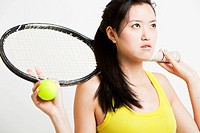 Thoughtful young woman holding tennis racket and ball over white background