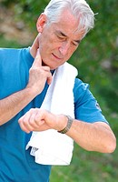60 years old man checking his pulse after physical activity.