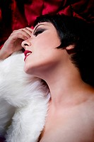 seminude beautiful short haired brunette woman lying on red silk with white fur, sensuous