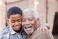 African American grandfather hugging grandson
