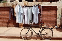 Galabayyas hanging on a clothes line on a street with a bike in Cairo, Egypt