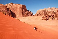A western tourist is rolling over a sand dune in in Wadi Rum