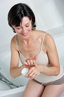 Woman applying moisterizing cream on her hands.