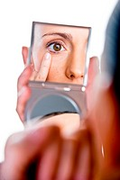 Young woman inspecting her eye in a mirror.