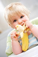 10 months old baby eating a banana.