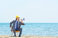 Man with hard hat and loudspeaker on beach