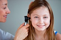 Doctor examining the ears of a 9 years old girl with an otoscope.