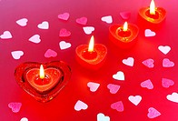 Valentine heart and candles on red background