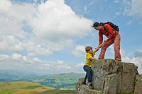Mother and son climbing rock formation