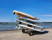 Calm waters of a lake or seaside inlet. A row of large bodyboards, surfboards, stacked on a trailer.