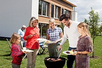 Germany, Bavaria, Nuremberg, Family standing around barbecue in garden